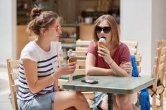 Horizontaler Schuss von recht jungen Frauen lecken die FruchtEiscreme, gekleidet in der Sommerkleidung, sitzen bei Tisch von der  lizenzfreie stockfotografie