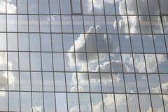 Horizontaler Schuss von Wolken reflektierte sich in den Fenstern eines modernen Bürogebäudes Lizenzfreie Stockfotografie