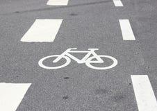 Horizontales Fahrradzeichen auf Asphalt mit weißen Streifen Stockfotos