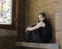 Horizontales Foto der erstaunlichen jungen Frau, die auf Steinbank sitzt lizenzfreies stockbild