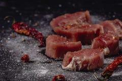 Horizontales Foto des rohen Schweinefiletfleisches Rohes Fleisch ist auf rustikalem dunklem Taktstockbrett, mit Pfeffer und Salz lizenzfreie stockfotos
