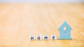 Horizontales Hauptwort von Würfelbuchstaben hinter blauem Haussymbol auf Holzoberfläche Lizenzfreie Stockbilder