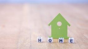 Horizontales Hauptwort von Würfelbuchstaben hinter Symbol des grünen Hauses auf Holzoberfläche Lizenzfreie Stockbilder