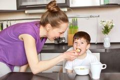 Horizontales Porträt der jungen Mutter in der zufälligen Ausstattung, Zufuhrkind mit Löffel, gibt ihm gesundes Lebensmittel, sich stockbilder