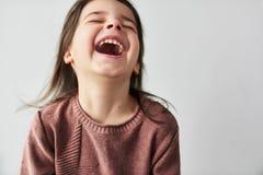 Horizontales Porträt der Studionahaufnahme des glücklichen schönen kleinen Mädchens, das frohe und tragende Strickjacke lokalisie lizenzfreie stockfotos