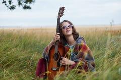 Horizontales Porträt der träumerischen Frau in der Sonnenbrille, welche die Akustikgitarre schaut aufwärts hält, träumend über Ge Stockbild