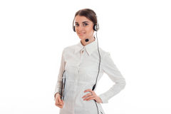 Horizontales Porträt des jungen netten Fernsprechamt-Arbeitskraftmädchens mit den Kopfhörern und Mikrofon, welche die Kamera betr Stockfotos