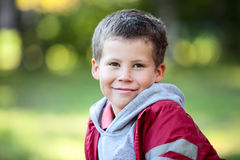 Horizontales Porträt des kaukasischen Jungen mit sechs Jährigen in der roten Jacke Stockbild