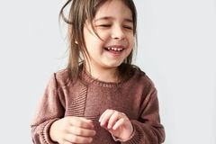Horizontales Porträt des Nahaufnahmestudios des glücklichen netten kleinen Mädchens, das frohe und tragende Strickjacke lokalisie stockfoto