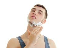 Horizontales Porträt eines jungen hübschen Kerls mit Schaum auf seinem Gesicht, das nah Ihre Augen rasiert Stockfoto