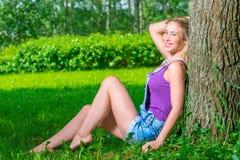 Horizontales Porträt eines schönen blonden Sitzens nahe einem Baum stockbild
