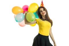 Horizontales Porträt eines schönen jungen Brunette, der in die Hand viele Ballone und Lächeln stieg lizenzfreies stockbild