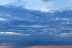 In the center, a strip of thick, crowded clouds. royalty free stock images