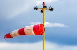 Horizontally flying windsock wind vane. With red and white lines against blue sky royalty free stock photos