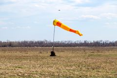 Horizontally flying windsock wind vane with red and yellow lines. Against blue sky stock photography