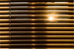 The sun passes through the blinds. Horizontally.Front. Naturally warm tone. Morning sunlight penetrates into the gap between the lamellas of sun blinds royalty free stock images
