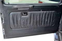 The horizontally opening trunk with scratches interior of the SUV old classic car pulled by black soft material leather in the stock images