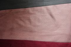 Horizontally sewn pieces of grey, pink and red artificial suede. Horizontally sewn pieces of gray, pink and red artificial suede Royalty Free Stock Photo