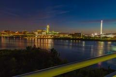 Horizonte céntrico de Omaha Nebraska en la oscuridad Puente del pie de Bob Kerrey sobre el río Missouri fotos de archivo