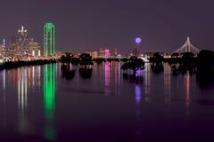 Horizonte de Dallas, Tejas en la noche a través del río Trinity inundado Imágenes de archivo libres de regalías