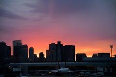 Horizonte de la ciudad, con un areoplane en la puesta del sol, con una visión colorida foto de archivo libre de regalías