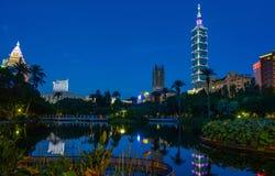 Horizonte de la ciudad de Taipei e iluminación de la noche que refleja en un lago pacífico después de puesta del sol Imagenes de archivo