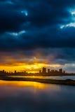 Horizonte de la ciudad en la salida del sol o puesta del sol con agua en primero plano Imagen de archivo