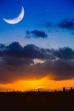 Horizonte de la ciudad en la salida del sol o puesta del sol con la luna y las estrellas Foto de archivo