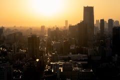 Horizonte de la ciudad en la puesta del sol con neblina Fotos de archivo