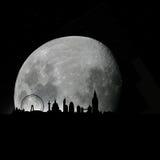 Horizonte de Londres por noche con la luna Imagenes de archivo