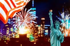 Horizonte de Manhattan en la noche y la estatua de la libertad fotografía de archivo
