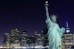 Horizonte de Manhattan y la estatua de la libertad en la noche Imagenes de archivo