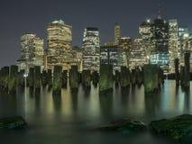 Horizonte de New York City en las luces de la noche Foto de archivo libre de regalías