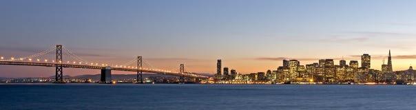 Horizonte de San Francisco con el puente de la bahía en la puesta del sol Fotos de archivo libres de regalías