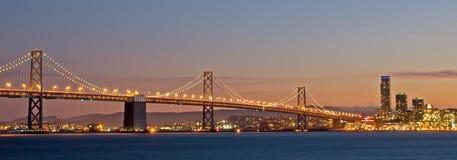 Horizonte de San Francisco con el puente de la bahía en la puesta del sol Foto de archivo