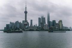 Horizonte de Shangai en un día nublado con los rascacielos cubiertos en nubes y niebla imagen de archivo libre de regalías