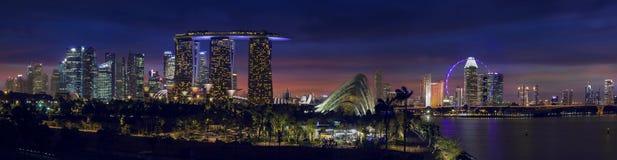 Horizonte de Singapur con los jardines por la bahía en el panorama de la oscuridad Fotografía de archivo