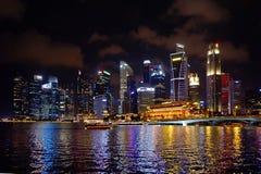 Horizonte de Singapur en la costa por noche Imagenes de archivo
