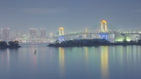 Horizonte de Tokio con la opinión de la noche del puente del arco iris imagenes de archivo