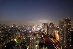 Horizonte iluminado de Tokio durante puesta del sol imagenes de archivo