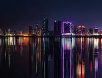 Horizonte moderno de la ciudad de la noche con las luces de neón y las reflexiones Imagenes de archivo