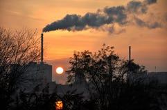 Horizontindustrie in einer kleinen netherland Stadt in Europa, mit einem großen Kamin und ein Rauch, Sonnenuntergang und Sonne al Lizenzfreie Stockfotografie