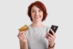 Horizotnal sköt av den nöjda kvinnan med försiktigt leende, rävaktigt hår, rymmer mobiltelefonen, och kreditkorten, gör pengartra fotografering för bildbyråer