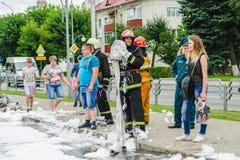 HORKI, БЕЛАРУСЬ - 25-ОЕ ИЮЛЯ 2018: Створки офицера 112 спасения пожарный рукав и разговаривать с улыбкой к молодой красивой девуш стоковое фото rf