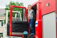 HORKI, BELARUS - 25 JUILLET 2018 : Le garçon regarde hors de la voiture rouge de service de délivrance 112 des vacances en parc u photos libres de droits