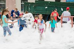 HORKI, BELARUS - JULY 25, 2018: Children of different ages play with airy white foam at the Rescue Service 112 holiday on a summer royalty free stock photo