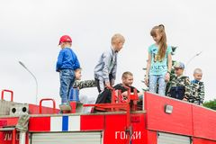HORKI, BELARUS - JULY 25, 2018: Children of different ages play on the red cars of the rescue service 112 on a holiday in the park royalty free stock image