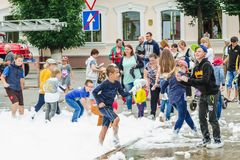 HORKI, BELARUS - JULY 25, 2018: Children of different ages play with white foam in the park at a party in summer day royalty free stock photo