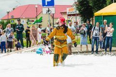 HORKI, BELARUS - JULY 25, 2018: Lifesaver of service rescue 112 pulls fire hose on a holiday in the park on a summer day stock photo