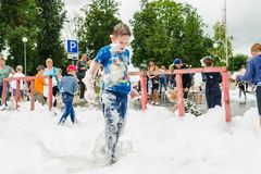 HORKI, BELARUS - JULY 25, 2018: A little fair-haired boy plays with airy white foam at the Rescue Service 112 holiday amid a crowd stock photos